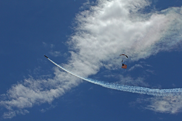 A sky diver with the American Flag being encircled by an acrobatic pilot at the opening of the Longmont air show Saturday, June 22, 2013 over Vance Brand Municipal Airport. (Photo submitted by Dennis Bennett)