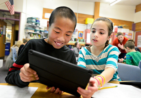 Fifth-graders Sam Chen, left, and Jamie Luna explore the Grand Canyon using Google Earth on an iPad at Ryan Elementary School in Lafayette on Wednesday, Jan. 16, 2013. <br /> (Greg Lindstrom/Times-Call)