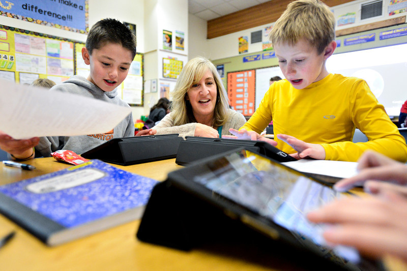 Fifth-grade teacher Holly Saltz, center, helps students Alex Bustamante, left, and Jack Battistelli with an exercise involving iPads and Google Earth at Ryan Elementary School in Lafayette on Wednesday, Jan. 16, 2013. <br /> (Greg Lindstrom/Times-Call)