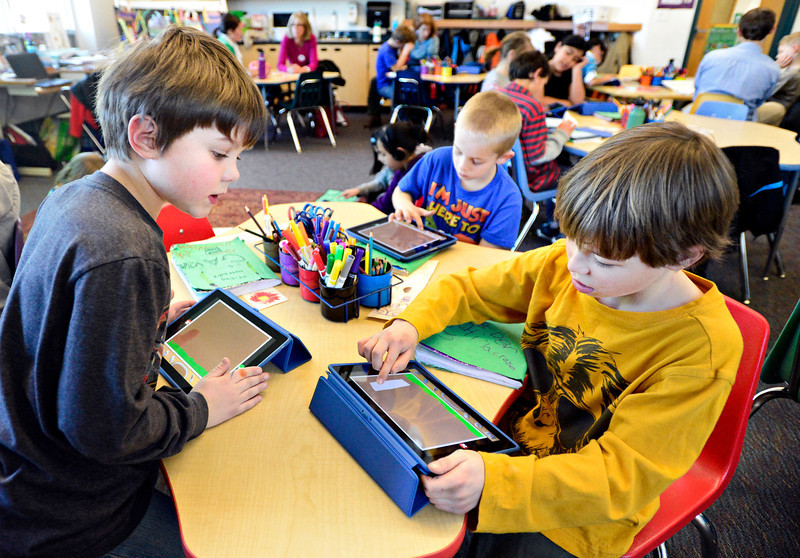 Third-graders, left to right, Gavin Caraway, Gavin Mitchell and Ben Perry draw pictures on their iPads at Ryan Elementary School in Lafayette on Wednesday, Jan. 16, 2013. <br /> (Greg Lindstrom/Times-Call)