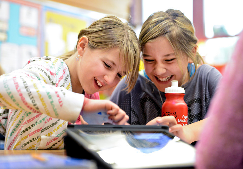 Fifth-graders Maddy Conley, left, and Deandja Warren laugh while exploring Google Earth on iPads at Ryan Elementary School in Lafayette on Wednesday, Jan. 16, 2013. <br /> (Greg Lindstrom/Times-Call)