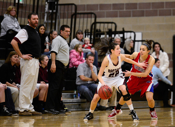 Silver Creek High School's Carrie Ramirez (No. 22) looks for an opening to pass while guarded by Centaurus High School's Shanlie Anderson (No. 5), Friday, Feb. 1, 2013, at SCHS. The Warriors defeated the Raptors, 51-47.<br /> (Matthew Jonas/Times-Call)