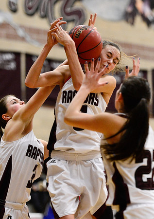 Silver Creek High School's Emilie Rembert (No. 5) grabs a rebound surrounded by teammates Margaret Davis (No. 3) and Carrie Ramirez (No. 22) in the game against Centaurus, Friday, Feb. 1, 2013, at SCHS. The Warriors defeated the Raptors, 51-47.<br /> (Matthew Jonas/Times-Call)