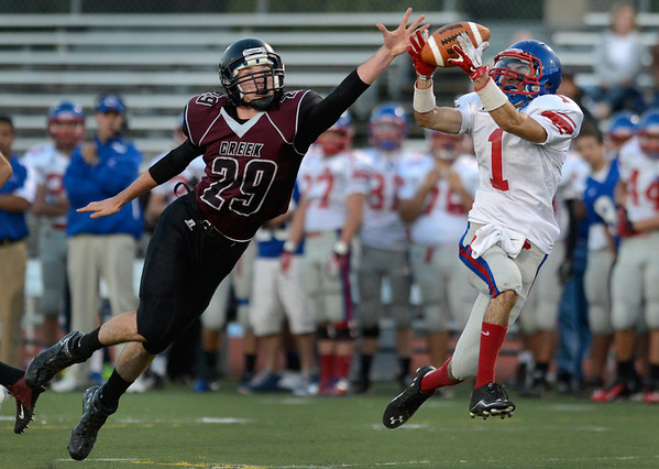 Centaurus High School's Matthew Wright (No. 1) completes the pass while followed by Silver Creek High School's Ross Fitzgerald (No. 29) during the first quarter, Friday, Sept. 7, 2012, at Everly-Montgomery Field in Longmont.<br /> (Matthew Jonas/Times-Call)