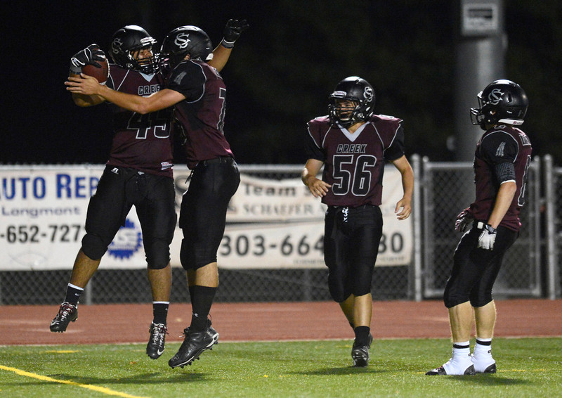 Silver Creek High School's Justin McLean (No. 45) celebrates a touchdown with teammate Jake Prinz (No. 75) during the fourth quarter, Friday, Sept. 7, 2012, at Everly-Montgomery Field in Longmont. The Raptors defeated the Warriors, 46-12.<br /> (Matthew Jonas/Times-Call)