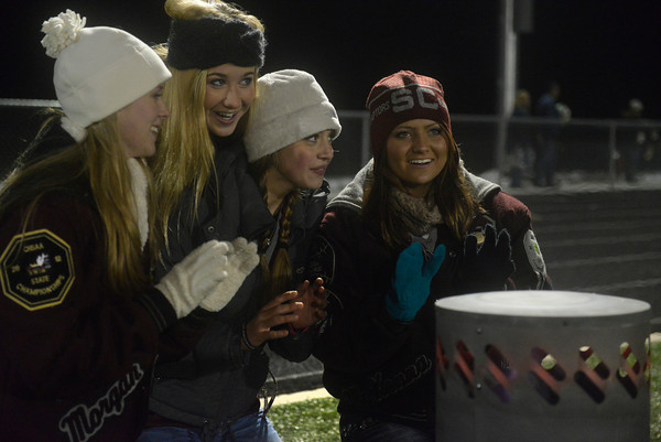 """From left, Silver Creek seniors, Morgan McKean, Dana Dow, Megan Foster, and McKenna Kostelecky sit by a propane heater before rushing the field after a victory against Mead Friday, Oct. 26, 2012, at Mead High School. Silver Creek beat Mead 35-6.  For more photos visit  <a href=""""http://www.BoCoPreps.com"""">http://www.BoCoPreps.com</a>.<br /> (Elaine Cromie/For the Times-Call)"""