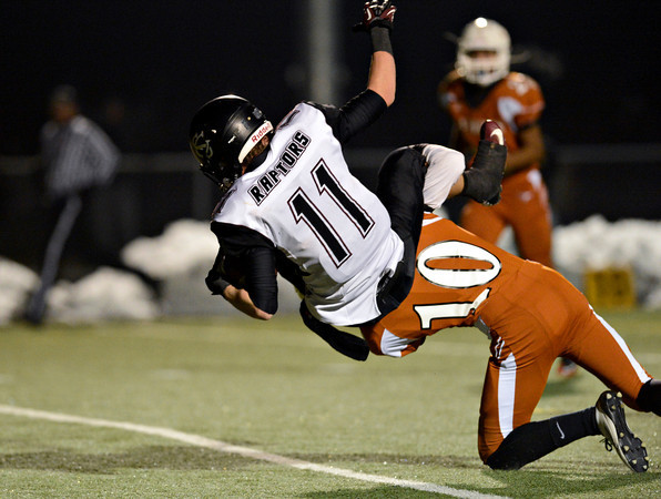 """Silver Creek's Zane Lindsey (11) goes over the top of Mead's Aaron Cheung (10) for a touchdown during the game at Mead High School on Friday, Oct. 26, 2012.  Silver Creek beat Mead 35-6.  For more photos visit  <a href=""""http://www.BoCoPreps.com"""">http://www.BoCoPreps.com</a>.<br /> (Greg Lindstrom/Times-Call)"""
