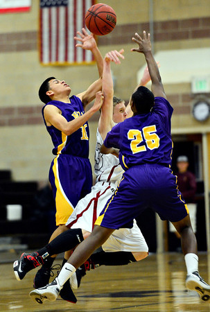 "Silver Creek's Steven Campbell (33) is fouled by Denver North's Ronnie Gilliam (25) and Ibashi Vandevelde (10) during the game at Silver Creek High School on Friday, Dec. 21, 2012. Silver Creek beat Denver North 61-39. For more photos from the game visit  <a href=""http://www.BoCoPreps.com"">http://www.BoCoPreps.com</a> <br /> (Greg Lindstrom/Times-Call)"