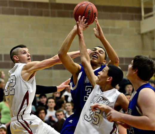 """Longmont's Kevin Mitchell is fouled while going up for a shot against Silver Creek's Luke Goforth, left, and Jordan Wright (35) during the game at Silver Creek High School on Tuesday, Jan. 29, 2013. Longmont beat Silver Creek 65-34. For more photos visit  <a href=""""http://www.BoCoPreps.com"""">http://www.BoCoPreps.com</a>.<br /> (Greg Lindstrom/Times-Call)"""