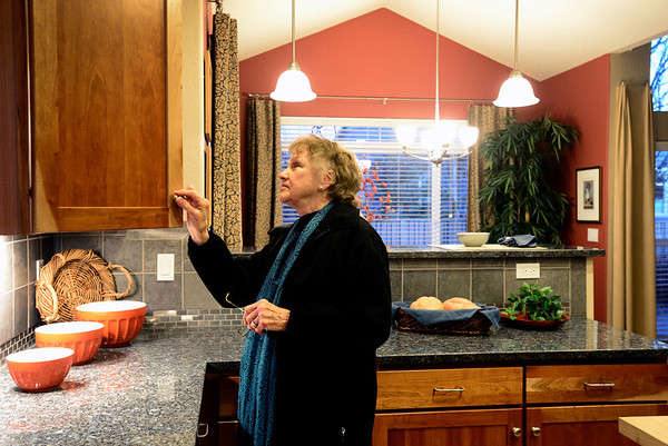 Home buyer Barbara McCormick checks out the cabinets inside the kitchen, Wednesday, Jan. 9, 2013, in Longmont.<br /> (Matthew Jonas/Times-Call)