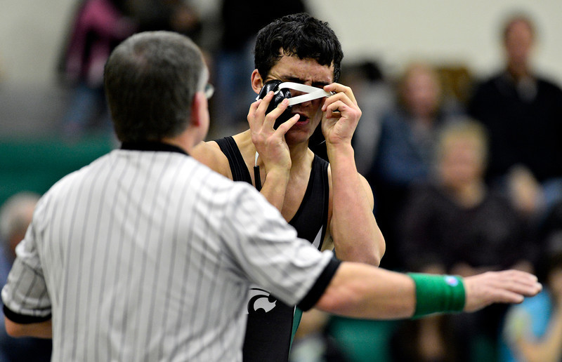 "Niwot's Matthew Strope tries to adjust his headgear during the match at Niwot High School on Wednesday, Jan. 9, 2013. For more photos visit  <a href=""http://www.BoCoPreps.com"">http://www.BoCoPreps.com</a>.<br /> (Greg Lindstrom/Times-Call)"