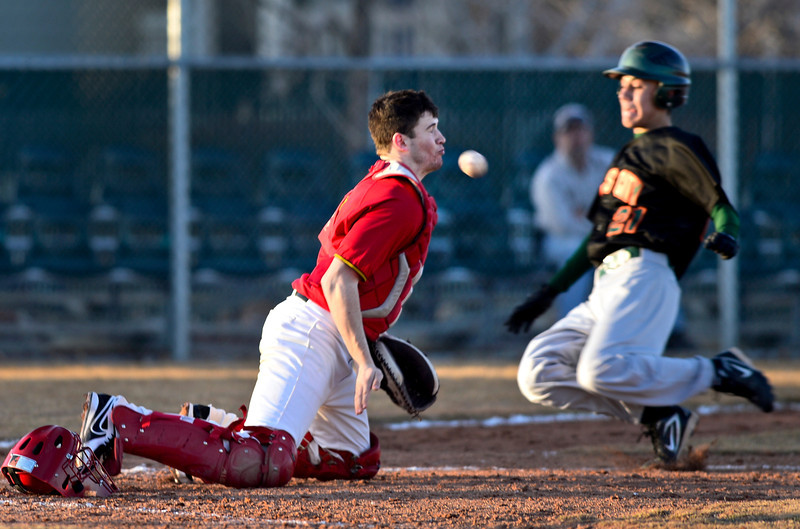 "Skyline catcher Garret Angstead tries to block a throw as Adams City's Eric Gomez slides safely into home during the game at Skyline High School on Thursday, March 7, 2013. Skyline beat Adams City 30-2. For more photos visit  <a href=""http://www.BoCoPreps.com"">http://www.BoCoPreps.com</a>.<br /> (Greg Lindstrom/Times-Call)"