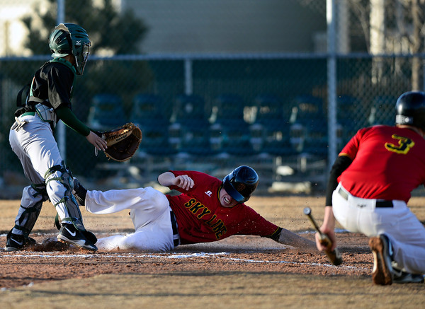 "Skyline's Adam Reigle slides safely into home past Adams City catcher Edgar Tulavera during the game at Skyline High School on Thursday, March 7, 2013. Skyline beat Adams City 30-2. For more photos visit  <a href=""http://www.BoCoPreps.com"">http://www.BoCoPreps.com</a>.<br /> (Greg Lindstrom/Times-Call)"