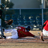 """Skyline's Adam Reigle slides safely into home past Adams City catcher Edgar Tulavera during the game at Skyline High School on Thursday, March 7, 2013. Skyline beat Adams City 30-2. For more photos visit  <a href=""""http://www.BoCoPreps.com"""">http://www.BoCoPreps.com</a>.<br /> (Greg Lindstrom/Times-Call)"""
