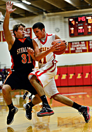 """Skyline's Aaron Soriano (11) tries to drive past Sterling's Dylan Manuello (31) during the game at Skyline High School on Friday, Dec. 7, 2012. For more photos visit  <a href=""""http://www.BoCoPreps.com"""">http://www.BoCoPreps.com</a>.<br /> (Greg Lindstrom/Times-Call)"""