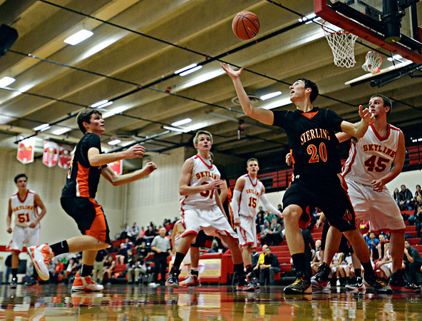 """Sterling's Collin Sanger (20) grabs a rebound over Skyline's Zach Anthony (45) during the game at Skyline High School on Friday, Dec. 7, 2012. Skyline lost 44-35. For more photos visit  <a href=""""http://www.BoCoPreps.com"""">http://www.BoCoPreps.com</a>.<br /> (Greg Lindstrom/Times-Call)"""