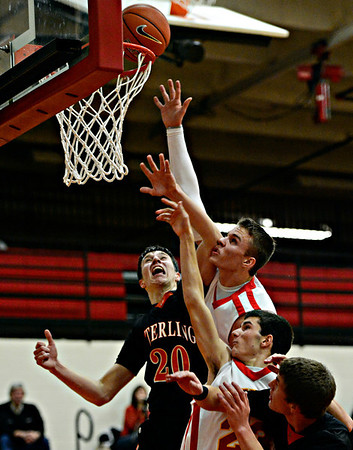 """Skyline's Colton Dabney stretches for a rebound over Sterling's Collin Sanger (20) during the game at Skyline High School on Friday, Dec. 7, 2012. For more photos visit  <a href=""""http://www.BoCoPreps.com"""">http://www.BoCoPreps.com</a>.<br /> (Greg Lindstrom/Times-Call)"""