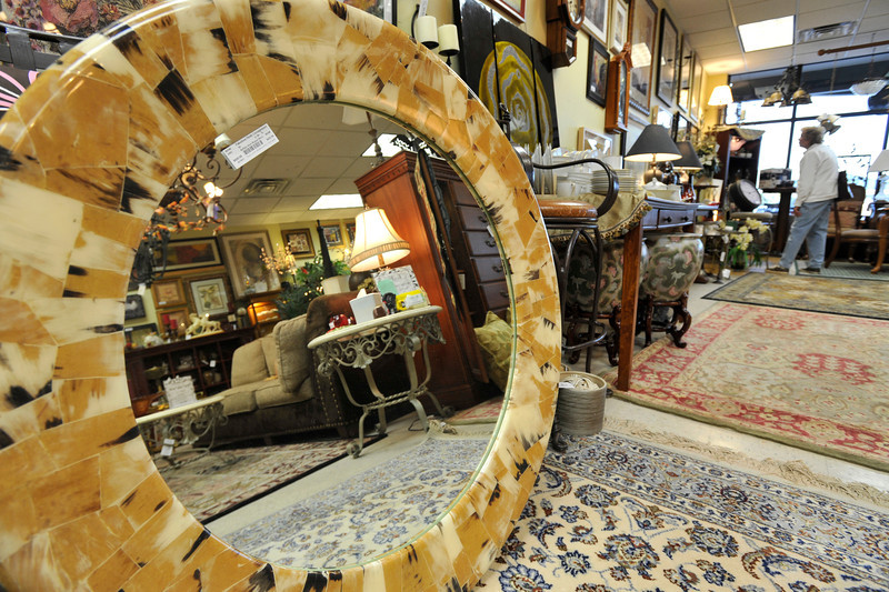 A large round mirror surrounded with pieces of buffalo horn is seen as a customer browses through home furnishings at Fabulous Finds Upscale Consignment, Friday, Nov. 23, 2012, in Longmont.<br /> (Matthew Jonas/Times-Call)
