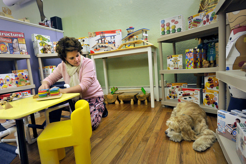 Co-owner Julie Johnson helps organize the childrens toy section of  Frames, Games & Things Unnamed while her dog Norman looks on, Friday, Nov. 23, 2012, on Main Street in Longmont.<br /> (Matthew Jonas/Times-Call)