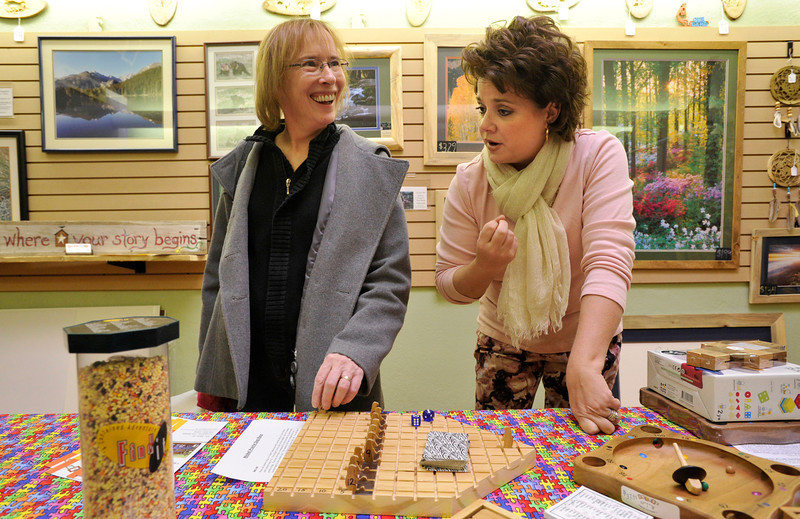 From left: Cathy Hirsch, of Longmont, talks with Julie Johnson, co-owner of Frames, Games & Things Unnamed on Main Street, Friday, Nov. 23, 2012, in Longmont.<br /> (Matthew Jonas/Times-Call)