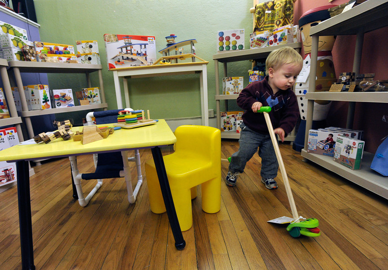 Tyler Carton, 20 months old, plays with a wooden push toy at Frames, Games & Things Unnamed on Main Street, Friday, Nov. 23, 2012, in Longmont.<br /> (Matthew Jonas/Times-Call)