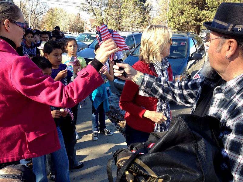 Marty Cottrell, right, a volunteer with the Boulder County Veterans Service office, hands out American flags before the start of the Veterans Day Parade in Longmont on Friday, Nov. 11, 2011. (Richard M. Hackett/Times-Call)