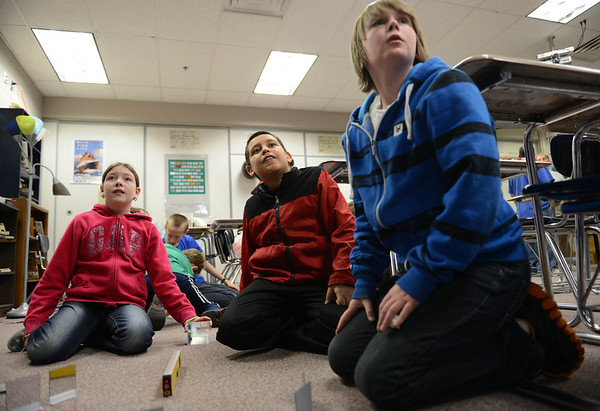 From left: Longmont Estates Elementary fifth grader Nita Creager, and Westview Middle School sixth graders Jeremiah Medina, and David New shine a laser onto a target during a light and laser physics demonstration Wednesday March 6, 2013 at Westview. (Lewis Geyer/Times-Call)
