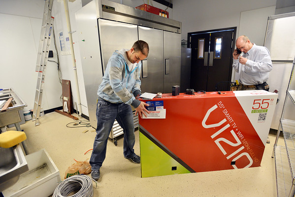 Electrician Dan Feiner, right, and his son Chris with Feiner Electric move a TV  to make room for a refrigerator in the back room of the new Ziggi's Coffee House at 104th Ave. and Federal Blvd. in Westminster on Thursday.<br /> February 14, 2013<br /> staff photo/ David R. Jennings