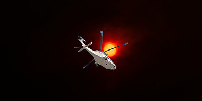 Dramatic Bushfire sunset sky with an airborne helicopter in the foreground. Sun glow over Gosford city through wildfire smoke and haze. Australia. 2019