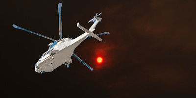 Dramatic Bushfire sunset sky with an airborne helicopter closeup in the foreground. Crimson orange sun glow through wildfire smoke and haze. Australia. 2019