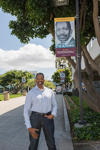 Alumnus Gil Ivey stands in front of his I'm a toro banner on campus at CSUDH