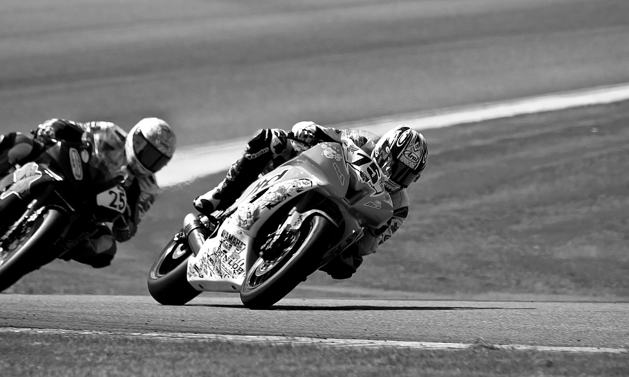 No. 75 pro motorcycle racer Huntley Nash leads No. 25 Joey Pascarella from Team DNA Energy Drink through a turn.