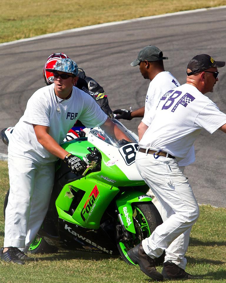 AMA Pro Racer Ben Young getting some help with his Fogi Racing Kawasaki after a crash at Barber Motorsports Park.