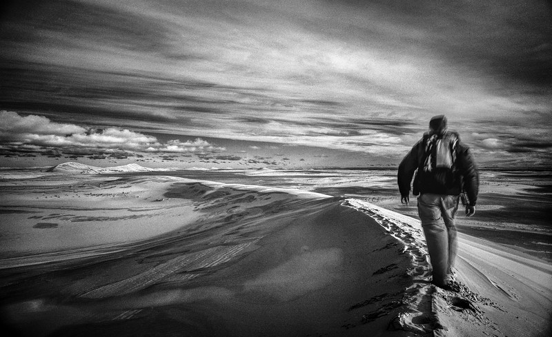 Hiker walking across the crest of a sand dune (Black and white)