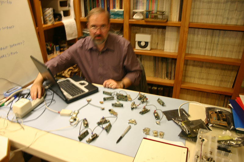 Stephen Moraco,  KC0FTQ,  lead on the Can-Do widgets for the P3E and Eagle spacecraft.  A pseudo-spacecraft of widgets is on the work desk.