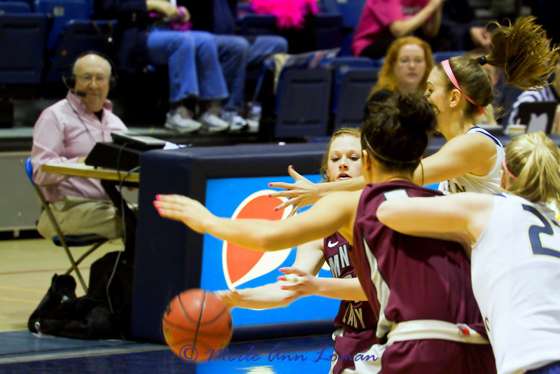 Kenzie De Boer passing to Sarah Ena. Tom Stage, voice of the Lady Griz, is in the background at the table broadcasting the game on the radio.
