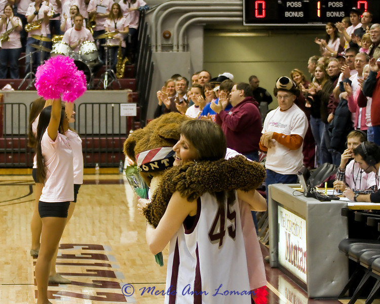 Jill Valley - breast cancer survivor and much loved local news anchor at the Lady Griz game in Dahlberg Arena, Missoula, MT, Feb 24, 2011. Montana Monte, the mascot, is giving her a hug.