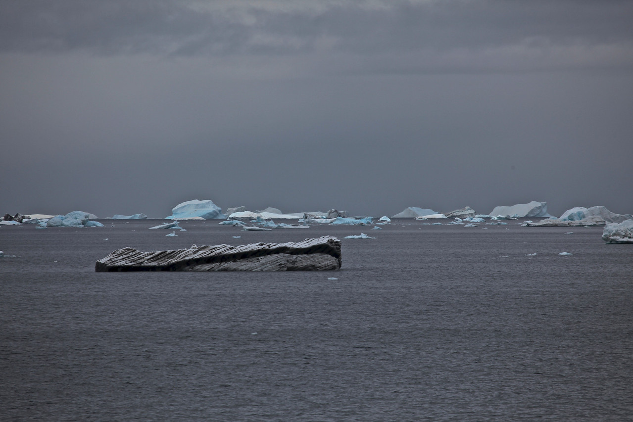 """While many of the icebergs are a pristine white, some like these are very dirty.  This can come from where they """"broke off"""" of the ice shelf as well as being due to weather."""