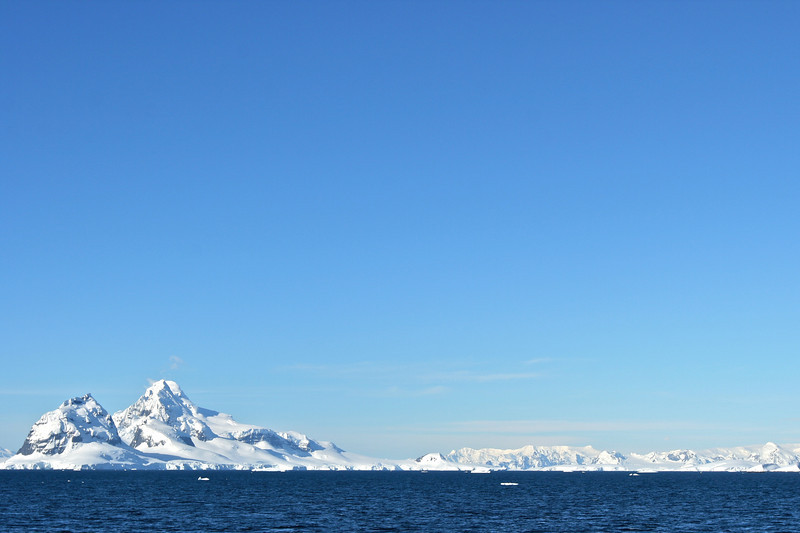 As our cloudless perfect Antarctic day continued, we sailed along the coast to Port Lockroy, with the Antarctic mountains in the distance.