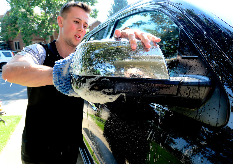zach sattler of anchor wash cleans the exterior as his team works on a car at