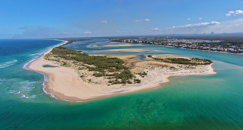 Blue water of the Pacific Ocean flow into Pumicestone Passage at the northern end of Bribie Island