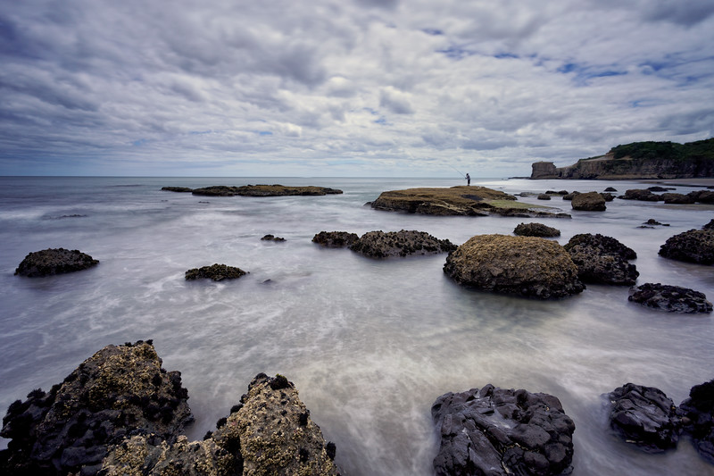Fisherman on rocks at low tide at Maori Bay, Muriwai west of Auckland