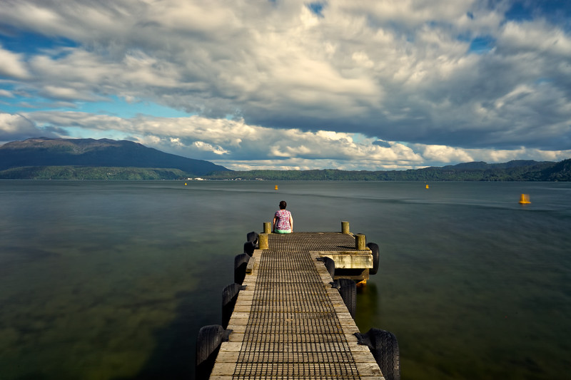 Girl on a jetty at Lake Tarawera, with Mt Tarawera volcano on left.