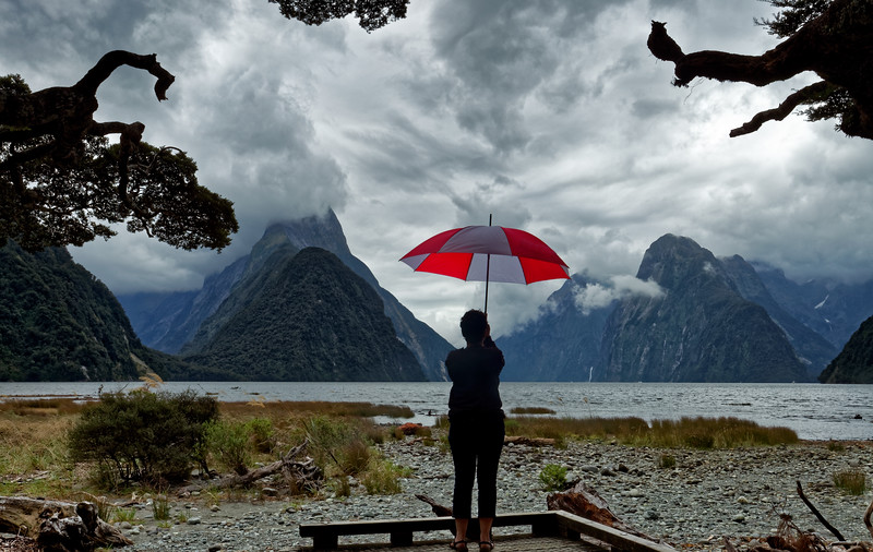 Girl with umbrella at Milford Sound in Fiordland National Park, one of the wettest places on earth