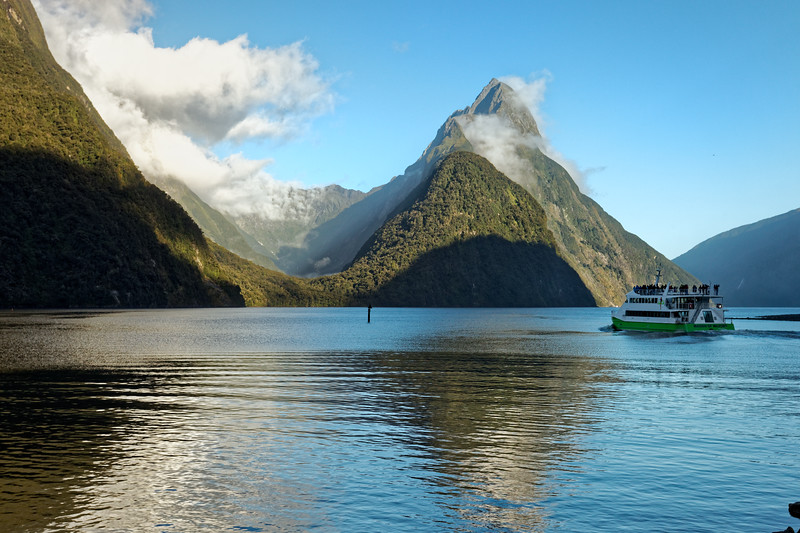 A tour boat sets our early at Milford Sound towards Mitre Peak in Fiordland National Park