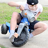 "Kevin Harvison | Staff photo<br /> Kell Hearod goes over on two wheels while he attempts to beat his old ""speed record"" after finding an old toy him and his friend played with years ago."