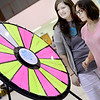 Kevin Harvison | Staff photo<br /> Kacie Cantrell, left with Compassion Pregnancy Center watches with Victoria Allen, right, to see what prize the wheel will land on during the Kids Fair held Saturday at the Southeast Expo Center.