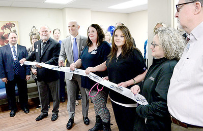 Kevin Harvison | Staff photo Pictured center, Dr. James L'Esperance, Urologic Specialist at Southeast Clinic speaks cuts a ribbon during a ceremony Thursday at their office located on the 2nd floor at 4 East Clark Bass Blvd.