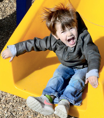 Kevin Harvison | Staff photo<br /> Excited, Mason Titsworth enjoys the sun and a hair raising experience as he goes down the a slide.
