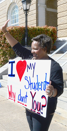 Kevin Harvison | Staff photo McAlester teacher Stephanie Walker holds a sign in front of the Carl Albert Federal Building Wednesday and waves to vehicles as they acknowledge her, a group of teacher and students; as a part of the State wide teacher walk out.
